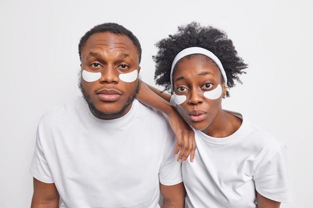 Foto de la novia y el novio sorprendidos de afro america miran atentamente a la cámara