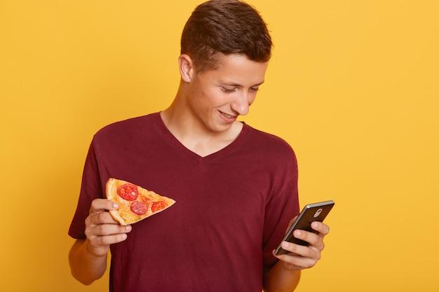 Foto de ocupado adolescente alegre curioso sosteniendo su teléfono inteligente, usando su dispositivo, revisando los sitios de redes sociales