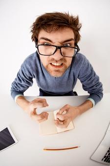 Foto de ojo de pez de hombre angustiado, molesto y enojado apretando las manos enojado mirando con los dientes apretados, frunciendo el ceño molesto, siéntese en el escritorio de la oficina