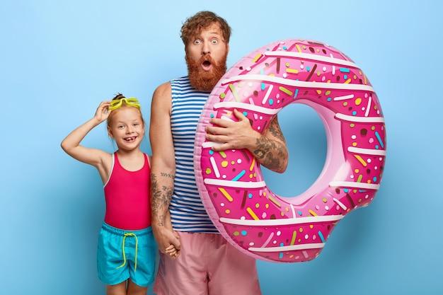 Foto de padre e hija de jengibre estupefactos posando en trajes de piscina