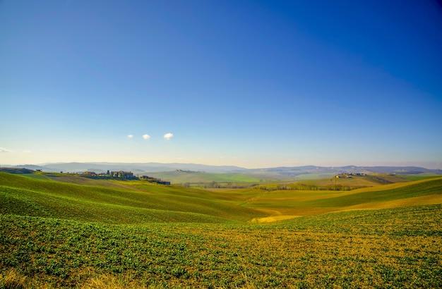 Foto de paisaje de un campo verde brillante y un cielo azul claro