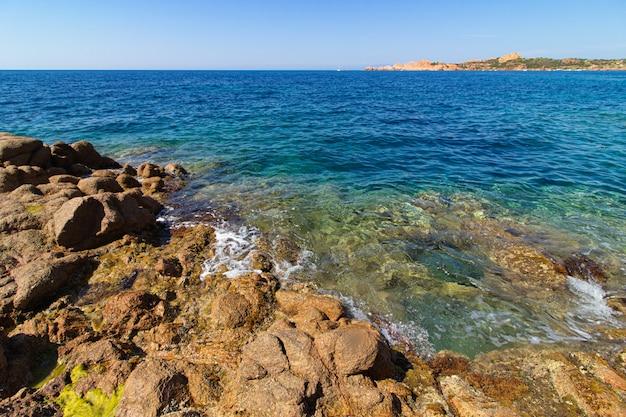 Foto de paisaje de grandes rocas, colinas verdes en un océano azul con un cielo azul claro