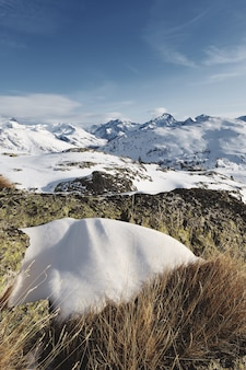 Foto panorámica de los alpes franceses cubiertos de nieve con el sol brillando bajo un cielo azul