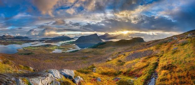 Foto panorámica de colinas cubiertas de hierba y montañas cerca del agua bajo un cielo nublado azul en noruega