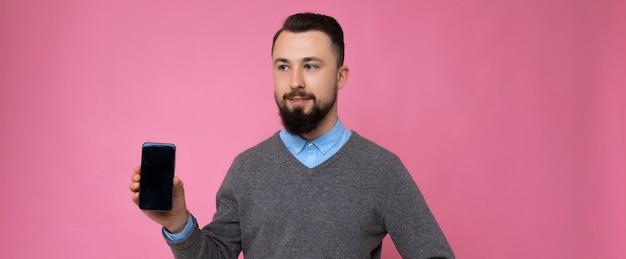 Foto panorámica de guapo feliz fresco joven morena sin afeitar hombre con barba vistiendo elegante suéter gris y camisa azul que se encuentran aisladas sobre fondo rosa pared sosteniendo teléfono inteligente y mostrando phon