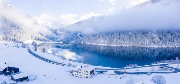Foto panorámica de hermosos árboles cubiertos de nieve con un lago tranquilo bajo un cielo brumoso