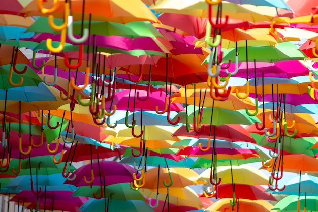Foto panorámica de un mar de coloridos paraguas colgantes
