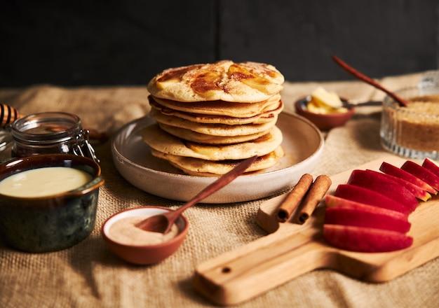 Foto de panqueques de manzana con manzanas y otros ingredientes sobre la mesa