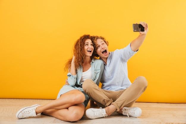 Foto de pareja alegre hombre guapo y mujer rizada sentados juntos en el suelo y tomando selfie en smartphone, aislado sobre fondo amarillo