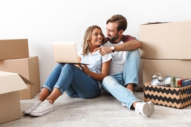Foto de pareja complacida en ropa casual usando y señalando con el dedo a la computadora portátil mientras está sentado cerca de cajas de cartón aisladas sobre una pared blanca