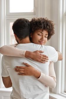Foto de pareja diversa abrazar unos a otros
