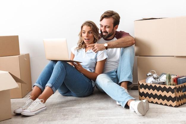 Foto de pareja emocionada en ropa casual usando y señalando con el dedo a la computadora portátil mientras está sentado cerca de cajas de cartón aisladas sobre una pared blanca