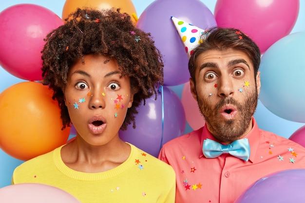 Foto de pareja joven asombrada posando rodeada de globos de colores de cumpleaños