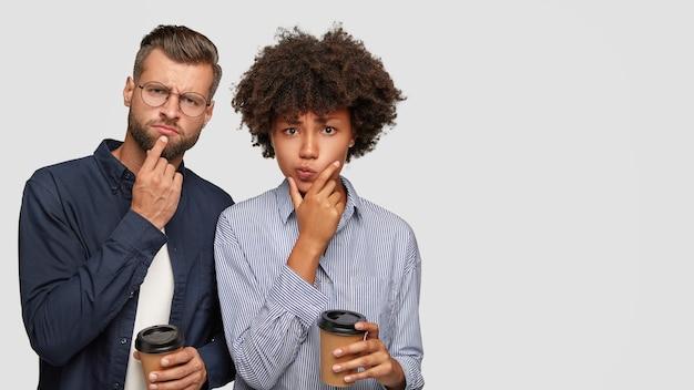 Foto de pareja joven multiétnica desconcertado pensativo mantenga barbillas