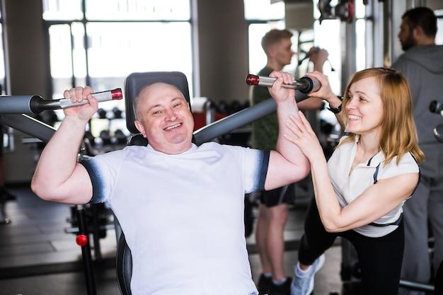 Foto de pareja mayor en el gimnasio. un hombre hace un ejercicio sobre sus brazos y hombros.