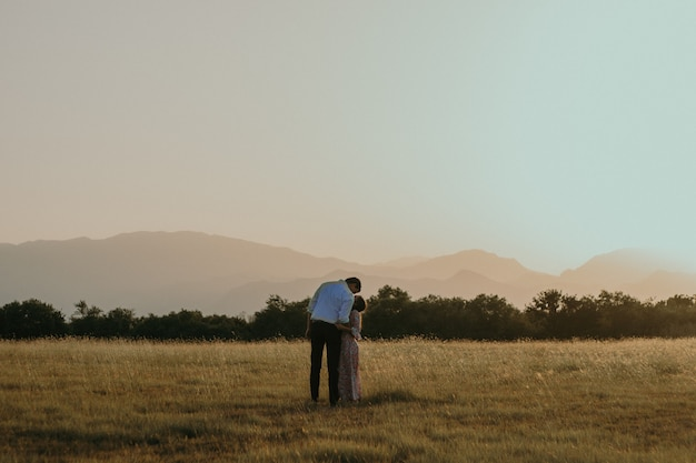 Una foto de una pareja desde la parte de atrás de pie en el campo y besándose