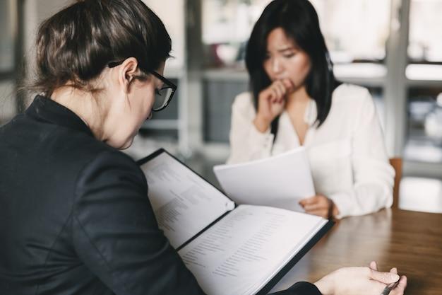 Foto de la parte posterior de la empresaria entrevistando y hablando con la solicitante nerviosa durante la entrevista de trabajo: concepto de negocio, carrera y colocación