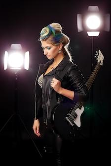 Foto de la parte posterior de un guitarrista femenino en chaqueta de cuero y pantalones de pie y jugando sobre fondo negro.
