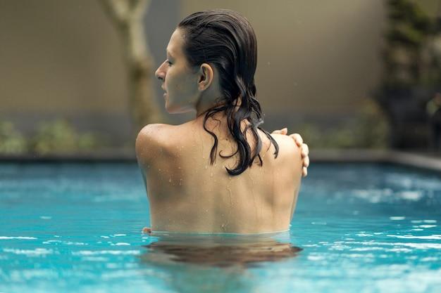 Foto de la parte trasera de una chica mojada en la piscina.