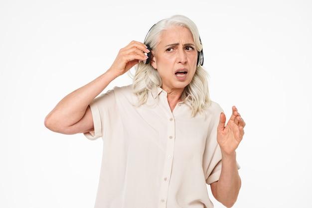 Foto de pensionista jubilada con cabello gris que se apaga los auriculares inalámbricos mientras escucha música y trata de escuchar, aislado sobre una pared blanca