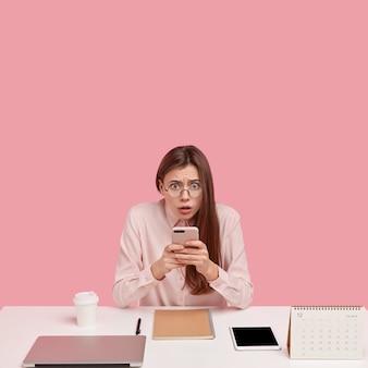 Foto de perfeccionista frustrado sostiene teléfono móvil, publica nueva publicación, edita fotos en redes sociales, se conecta a internet inalámbrico, usa anteojos
