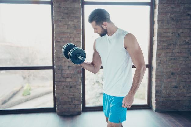 Foto de perfil de chico guapo con barba entrenamiento matutino músculos bíceps levantar pesas pesas ropa deportiva pantalones cortos sin mangas casa de entrenamiento grandes ventanales en el interior
