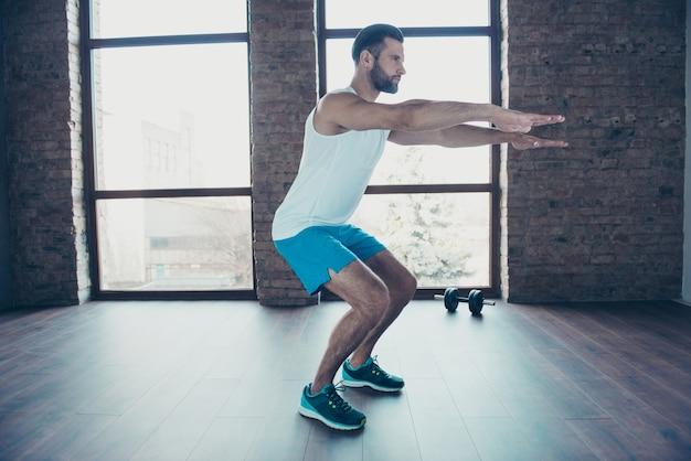 Foto de perfil de cuerpo entero de macho haciendo sentadillas estáticas proceso de quema de grasa ropa deportiva pantalones cortos sin mangas zapatillas de deporte casa de entrenamiento cerca de grandes ventanales en el interior