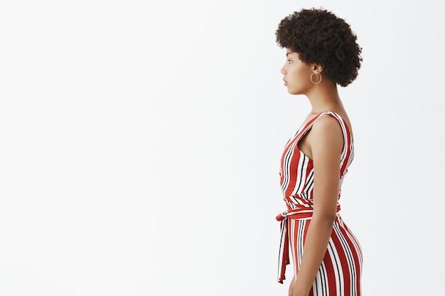 Foto de perfil de elegante y atractiva mujer afroamericana moderna con un mono de rayas de moda con peinado afro, mirando a la izquierda con una mirada tranquila informal sobre la pared gris
