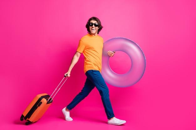 Foto de perfil de longitud completa del hombre paso mantener el equipaje flotador anillo usar camiseta naranja jeans gafas de sol calzado aislado fondo de color rosa