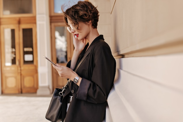 Foto de perfil de mujer fresca con pelo corto en chaqueta negra tiene tableta al aire libre. hermosa mujer de anteojos con bolso posando en la calle.