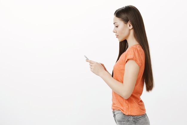 Foto de perfil de mujer morena bastante joven mediante teléfono móvil, compras en línea, mediante la aplicación de teléfono inteligente