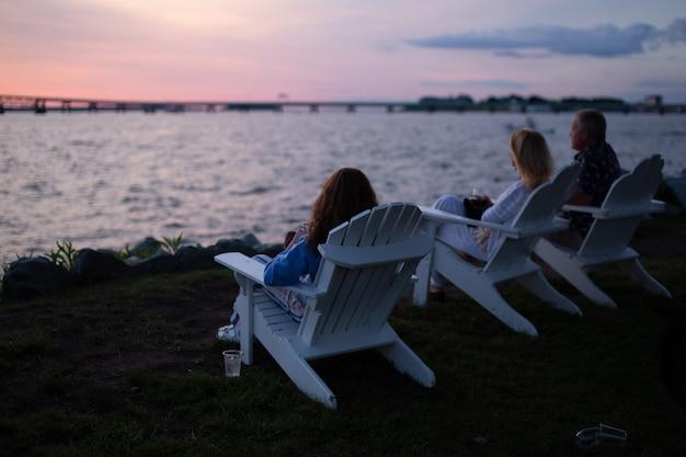 Foto de personas sentadas en sillas blancas a través del cuerpo de agua