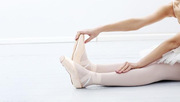 Foto de los pies de la hermosa bailarina durante el estiramiento
