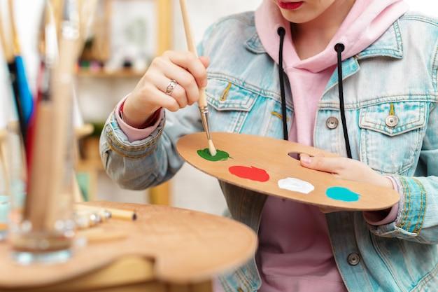 Foto de pintura de joven artista femenina en estudio