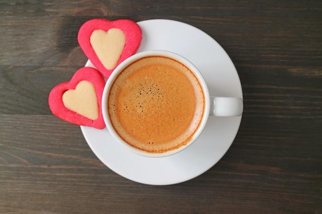 Foto plana de café exprés con dos galletas en forma de corazón sobre una mesa de madera de color marrón oscuro