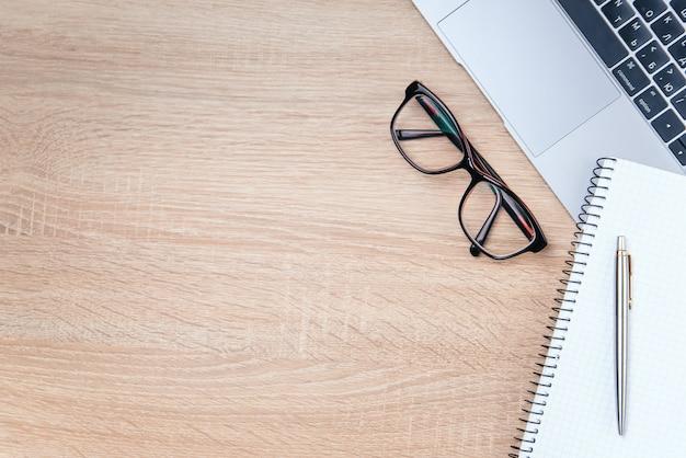 Foto plana del escritorio de oficina de madera con laptop, anteojos, bolígrafo y cuaderno con copia espacio de fondo.