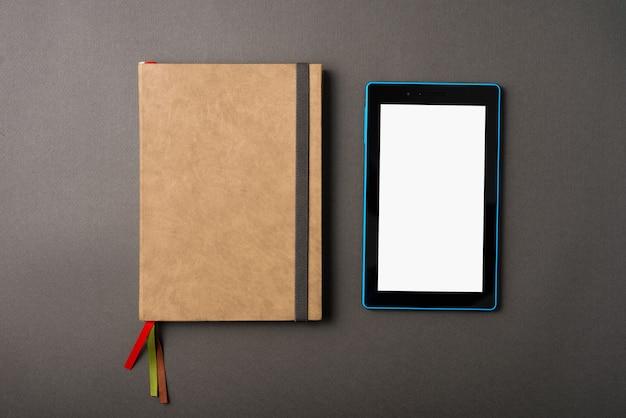 Una foto de un planificador y una tableta cerca de él en una mesa oscura
