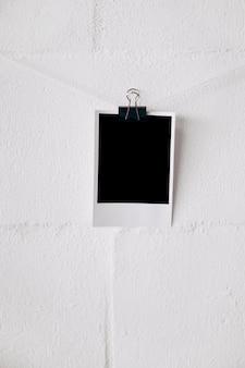 Foto polaroid en blanco en la cadena adjunta con clips de papel bulldog contra la pared blanca