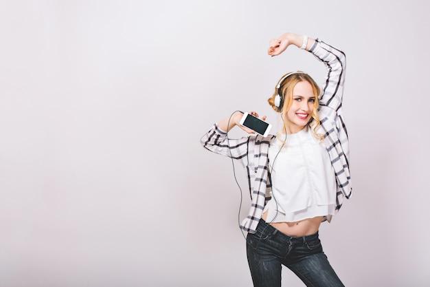 Foto positiva emocional linda chica con smartphone, disfrutando de su vida, escuchando música favorita, bailando contra la pared gris. concepto de ocio y tecnología. buen humor.