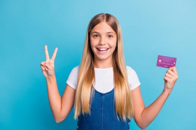 Foto de positivo lindo cabello rubio jovencita mantenga la tarjeta bancaria mostrar v-sign use ropa casual aislado sobre fondo de color azul pastel