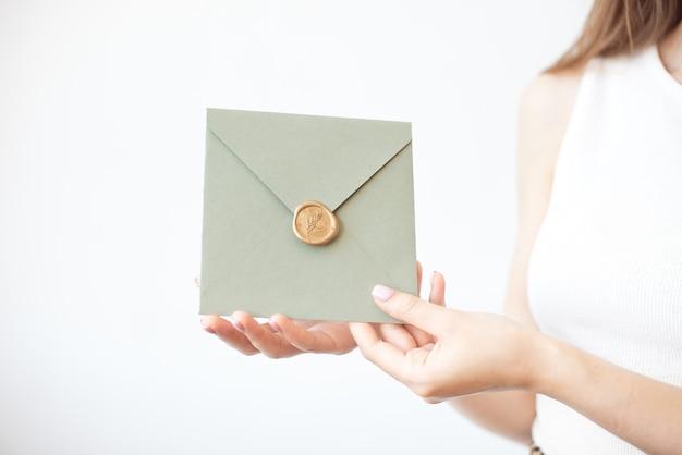 Foto del primer de las manos femeninas que sostienen el sobre de la invitación con un sello de la cera, un certificado de regalo, una postal, una tarjeta de la invitación de la boda.