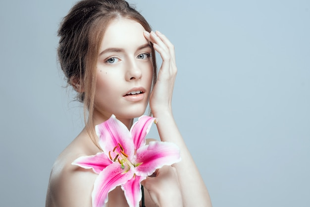 Foto del primer de una muchacha hermosa con una flor del lirio.