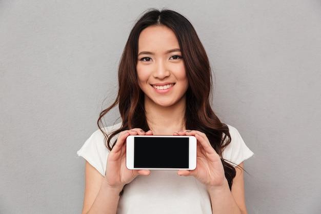 Foto del primer de la mujer asiática sonriente con el pelo largo y castaño que muestra la pantalla copyspace del teléfono inteligente moderno, aislado sobre la pared gris