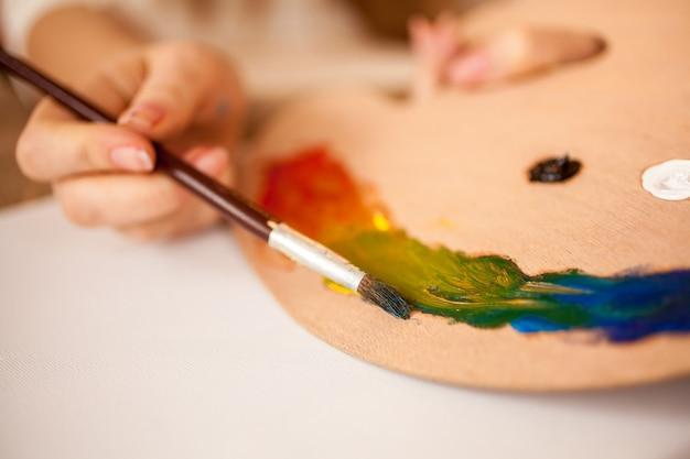 Foto en primer plano del arco iris de dibujo infantil con pintura al óleo sobre paleta de madera