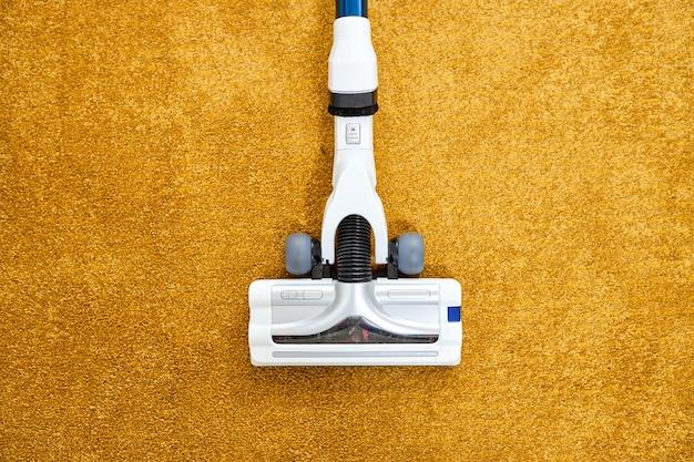 Foto de primer plano de la aspiradora aplicada sobre una alfombra amarilla en casa quitando el polvo, limpieza en casa, servicio de limpieza