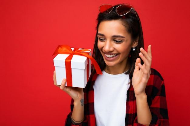 Foto en primer plano de la atractiva mujer morena adulta sonriente feliz aislada en la pared de fondo rojo