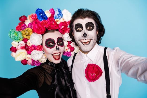 Foto de primer plano de la bonita pareja de demonios hombre dama abrazo tomar selfie emocionado octubre viaje latino usar vestido negro muerte traje rosas diadema tirantes aislado fondo de color azul