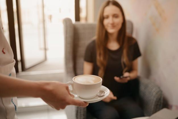 Una foto de primer plano de un café con leche que una mujer barista le ofrece a una niña en una cafetería.