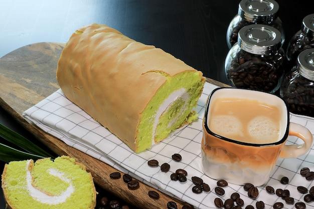 Foto de primer plano café recién hecho en la taza de color marrón y blanco con granos de café, y pandanus yam roll cake con crema blanca en el interior.