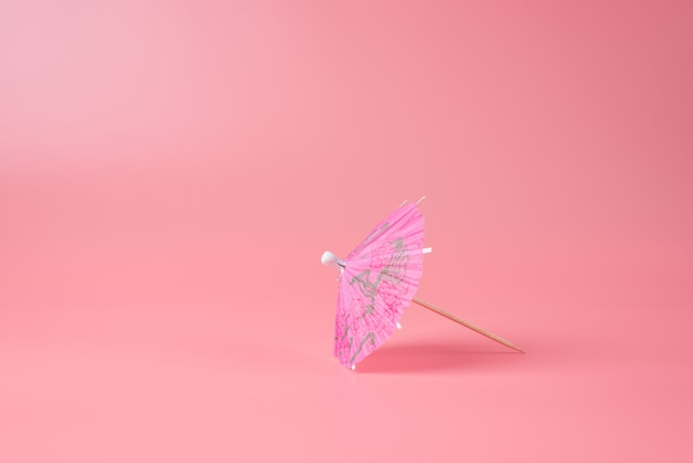 Foto de primer plano de cóctel paraguas rosa aislado sobre fondo rosa